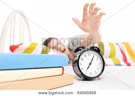 Sleepy man reaching for the alarm clock isolated on white background