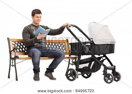 Young man holding a baby stroller and reading book isolated on white background