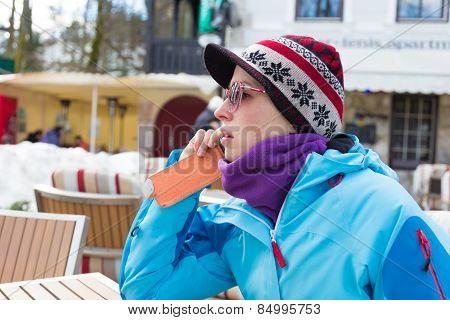 Woman in ski resort using smartphone.