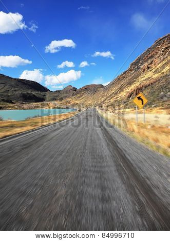 A trip at high speed. Dangerous driving in the national park Torres del Paine, Chile. A gravel road runs by the lakeside