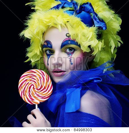 Girl with with creative make-up holds lollipop. Doll style.