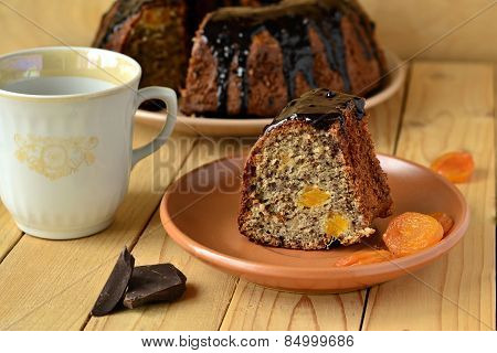 Banana fruitcake with dried apricots in chocolate glaze