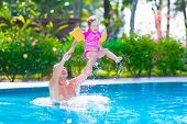 picture of swimming pool family  - Happy active family young father and his cute daughter adorable toddler girl playing in a swimming pool jumping into the water enjoying summer vacation in a beautiful tropical island resort - JPG