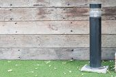 picture of lamp post  - Lamp post against a textured wood wall - JPG