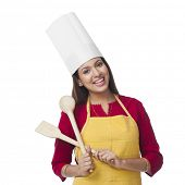 picture of ladle  - Portrait of a happy woman holding a spatula and ladle - JPG