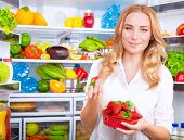 stock photo of strawberry blonde  - Portrait of cute blond woman standing near open refrigerator full of fruits and vegetables and eating fresh red ripe strawberries - JPG