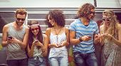 image of happy day  - Hipster friends using their phones on a summers day - JPG