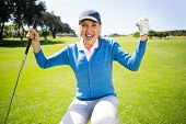 image of ladies golf  - Kneeling lady golfer cheering on putting green on a sunny day at the golf course - JPG