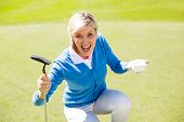 picture of ladies golf  - Excited lady golfer cheering on putting green on a sunny day at the golf course - JPG