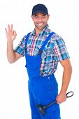 stock photo of plumber  - Portrait of happy plumber with plunger gesturing okay on white background - JPG
