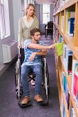 foto of classmates  - Smiling disabled student with classmate in library at the university - JPG