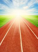 stock photo of track field  - Running track in field with sky and clouds  - JPG
