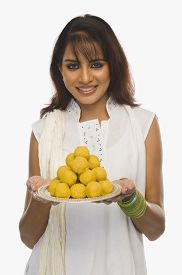picture of laddu  - Woman holding Laddu in a plate on Holi - JPG