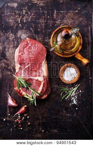 Raw Fresh Meat Steak Ribeye And Seasonings On Dark Metal Background