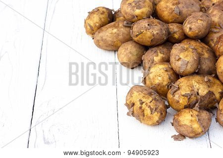 Unwashed new potatoes on white.