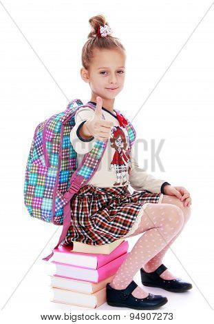 Serious, elegantly dressed schoolgirl sitting on a stack of book