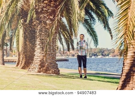 Healthy lifestyle young sporty woman having break between palm trees after jogging at tropical park