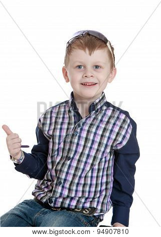 Stylish little blond boy in a plaid shirt and jeans held up the