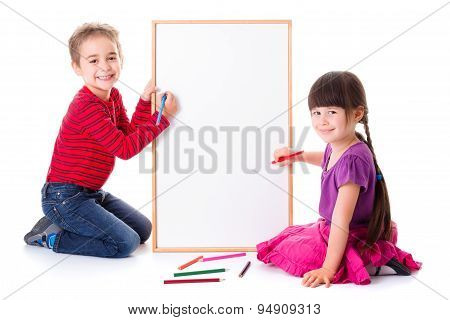 Pretty Little Girl And Boy Drawing On Board