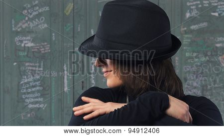 Adult Woman With A Hat Sitting In Front Of A Door In Italy