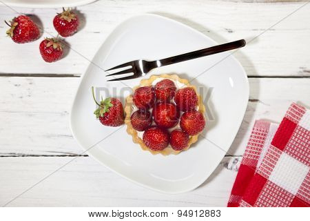 Strawberry tartlet on wooden table, top view