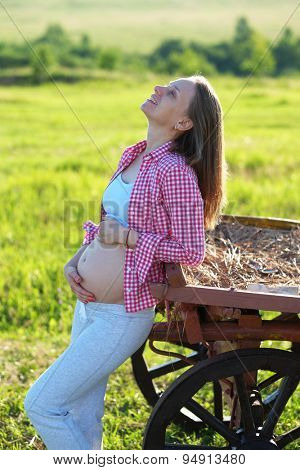Pregnant woman outdoors at sunny summer day
