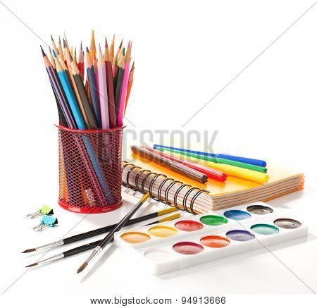 School equipment with pencils, notebook,  paints and brushes isolated on white.  Back to school concept.