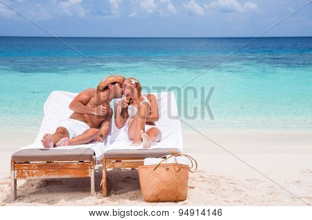 Happy couple kissing on beach resort, tanning on sunbed and eating tasty sweet ice cream, enjoying summer time on beautiful sea coast