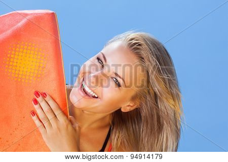 Closeup portrait of beautiful happy blond woman with surfboard on blue sky background, enjoying water sport, summer activity and holidays