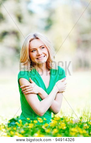 Beautiful young woman sitting on flower field