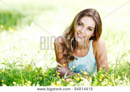 beautiful young woman in blue dress lying on grass
