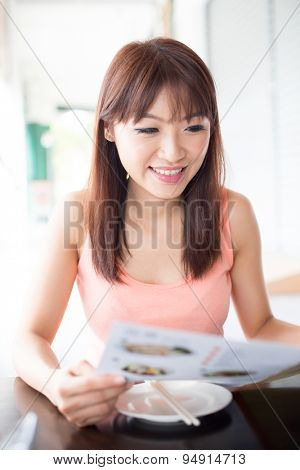Asian girl looking at menu and ordering foods in restaurant. Young woman living lifestyle.
