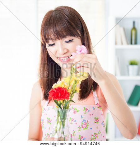 Happy Asian housewife with apron arranging flowers to vase. Young woman indoors living lifestyle at home.