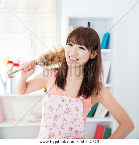 Happy Asian housewife with apron housekeeping, hand holding a duster and smiling. Young woman indoors living lifestyle at home.