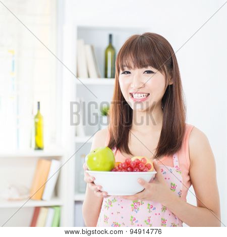 Happy Asian housewife with apron holding a bowl of fresh fruits. Young woman indoors living lifestyle at home.