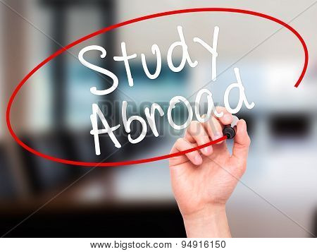 Man Hand writing Study Abroad with black marker on visual screen.