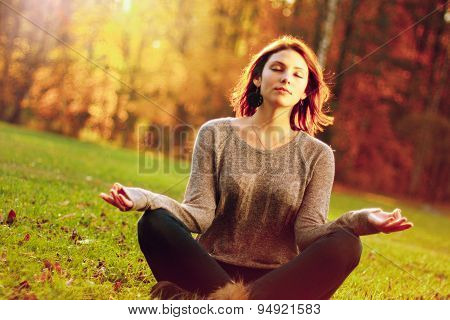 young girl meditating in autumn park