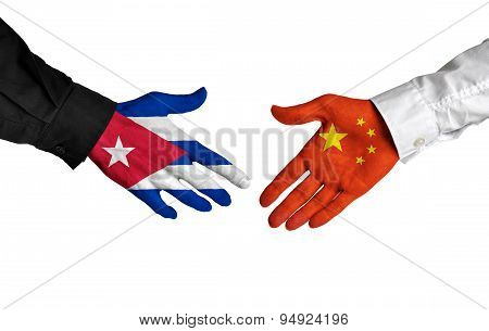 Cuban and Chinese leaders shaking hands on a deal agreement