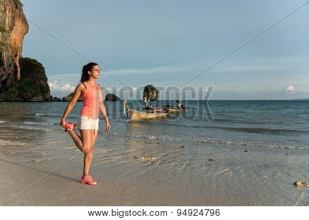 Woman Stretching Before Running At The Beach