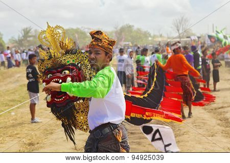 Balinese Man  Holding Kite With Dragon Head And Long Tail