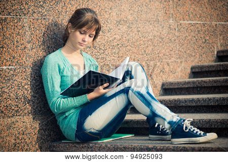 Girl sitting on stairs and reading note
