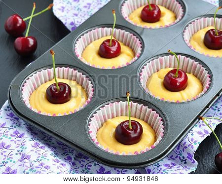 A tray of raw muffins with cherry. Ready for insertion into the oven.