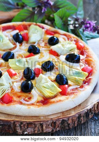 Healthy pizza with artichokes, olives, onions, peppers, basil and olive oil