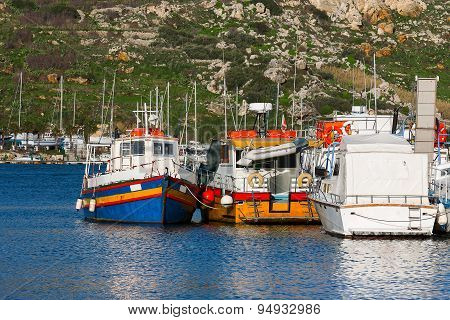 Colorful Traditional Fisher Boats At A Pier. Port Of Mgarr, Gozo Island, Malta.