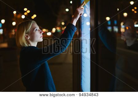 Attractive woman using sensitive screen of smart bus stop in Barcelona while standing at night city