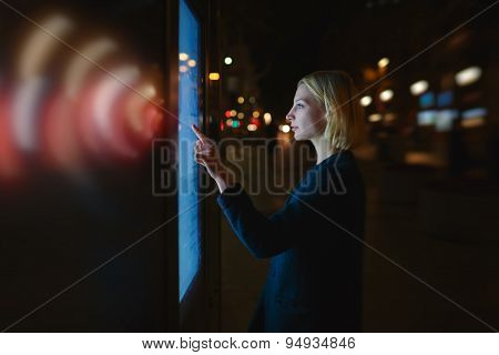 Female with wireless sign symbol of lights touching big digital screen of automated teller machine