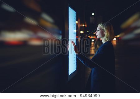 Young female using automated teller machine with big digital screen while standing in night city