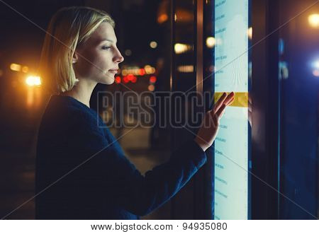 Woman verifies account balance on banking application via modern device while standing in night city
