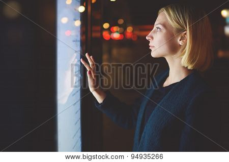 Smart city technology concept young woman using modern urban application of bus stop in Barcelona