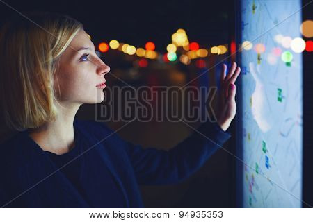 Stylish young woman standing front big digital screen with basic city street map GPS data
